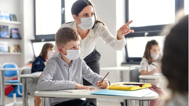 Un insegnate con la mascherina aiuta un suo alunno
