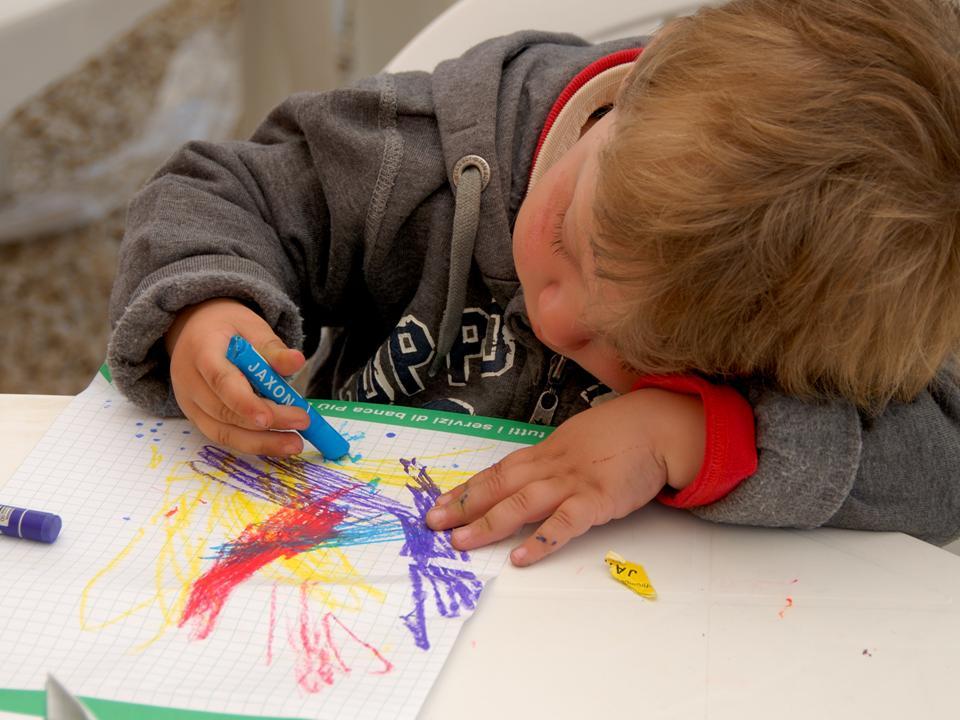 Un bambino disegna con i colori dell'arcobaleno