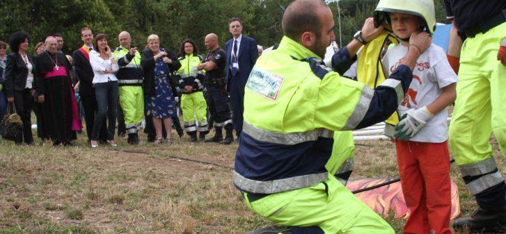 Un soccorritore mette un elmetto sulla testa di un bambino
